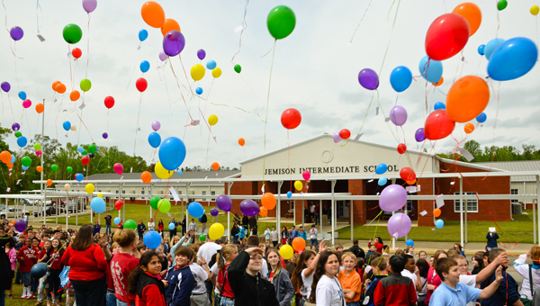Up and away: Jemison Middle School students wrote messages to their late classmate Christopher Rico and tied them to balloons that were released at the school.