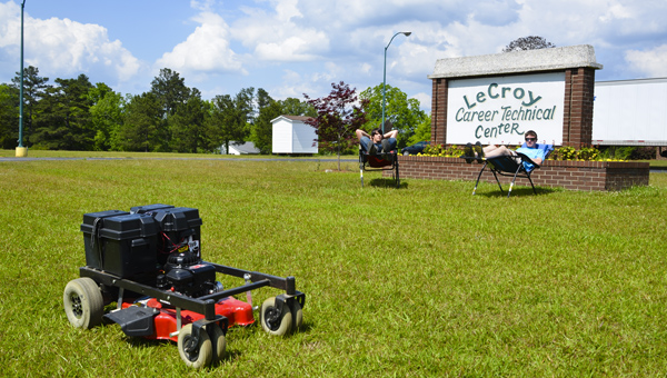 Robotics students Trevor Moon, left, and Chase Minor sit back as Minor guides the automated lawnmower across the grass at the career tech center.