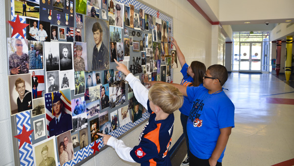 Third graders Jack Ellison, Isaiah Davidson and Mattie Cleckler point to the photographs of their relatives on the veterans' honor board at Clanton Intermediate School.