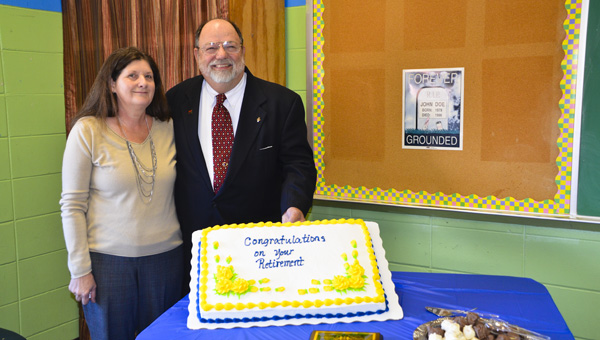 Randy Strattis, right, and wife Jeanie stand with his cake at a party Thursday celebrating his retirement from the SPAN Program of Chilton County.