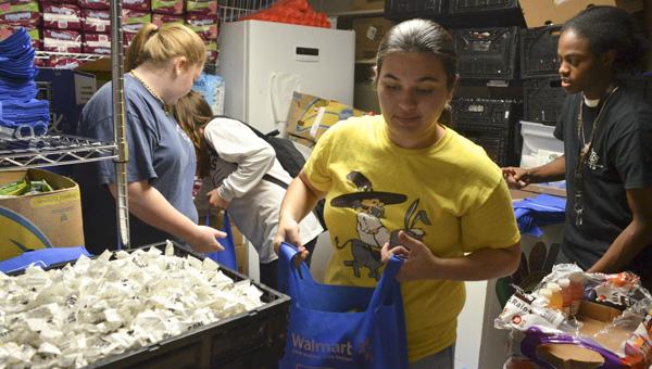 Jemison senior Courtney Burnette, junior Mikayla Thornton and junior Raeshon Jones volunteered their time to help families in need on Friday.