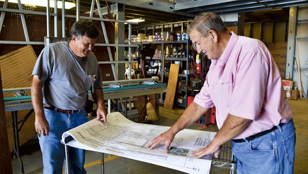 Chilton County Schools Maintenance Supervisor Wayne Howell (right) looks over plans for school reroofing projects with department employee Keilan Gore.