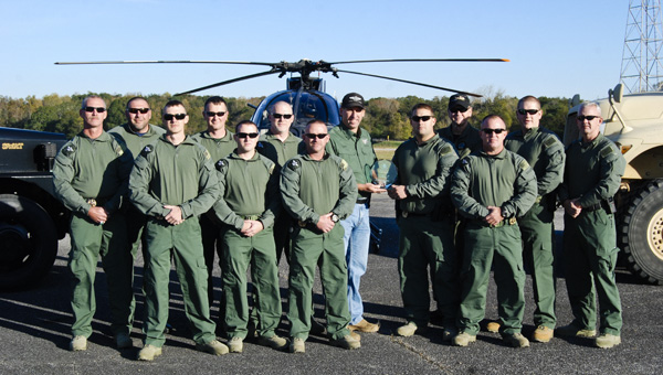 Members of the Chilton County Sheriff's Department SWAT Team display their crystal trophy for placing first at the 2013 Alabama Officer