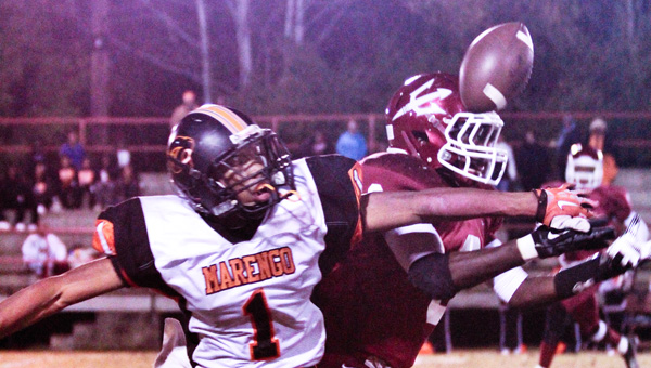 Fight for it: Maplesville's Damian Mitchell (right) and Marengo's Jamarkus Pritchett compete for a pass during Friday's first-round playoff game at George Walker Jr. Stadium.