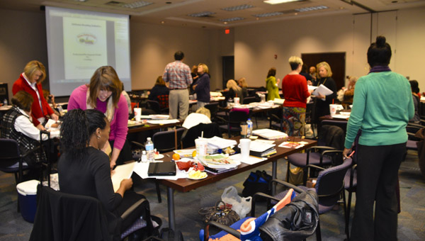 Regional staff members of the Alabama Reading Initiative go over their notes with each other during a break at a professional training session held at the Alabama Power building in Clanton last week.