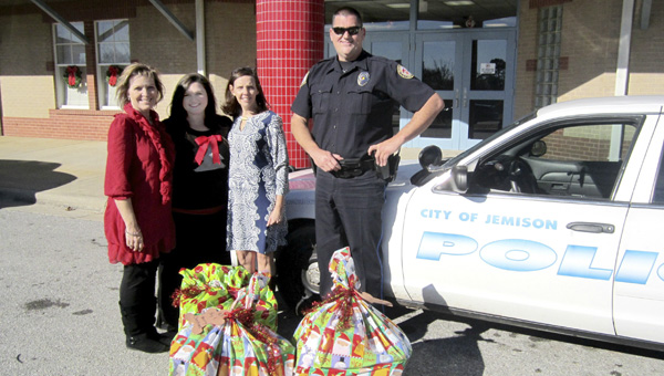 Members of the Jemison community helped collect toys for the Jemison Christmas for Kids drive. Jemison Librarian Tammie McGriff (far left), Jemison Elementary School counselors Kara Cleckley and Teresa Knott and Andy Sutley with the Jemison Police Department stand near bags of donated toys for eight local children in need.