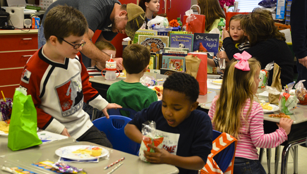 Nyzaiah DeJarnett opens a gift he received during his class' Christmas party at Clanton Elementary School on Thursday.