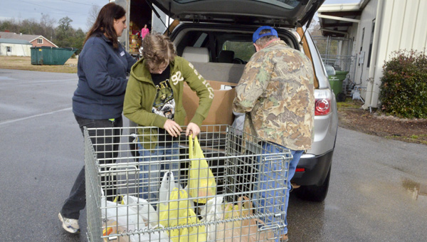 Ginger Luker (far left), Brian Hicks (center) and Wallace Cleckler unload donated items to the Chilton County Emergency Assistance Center in Clanton on Friday. The items were donated by the Judicial Correction Services in Jemison who held a canned food drive at their office during November and December as a way to give back to the community for the holiday season.