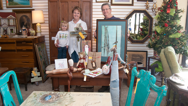 Available art: 2-year-old Melody Cheshire (far left) helps her grandmother and artist Kathy Hopper (center), and Tradewinds owner Charlie Schoenvogel, display works for sale at the shop.