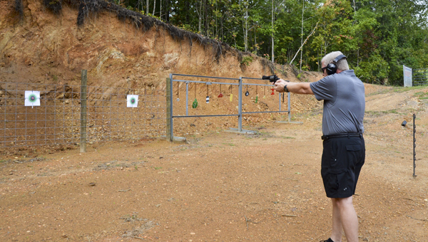 : Rocky Mount United Methodist Church Pastor Phil Guin practices shooting a target at the gun range located behind the church. (Photos by Emily Reed)