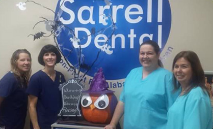 Contest entry: Sarrell employees Jamie Ezell, Doris Wade, Katrina Wilmon and Sarah Bowman stand with the owl-themed pumpkin created by the local office. (Contributed)