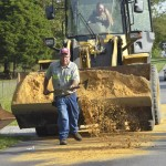 Clean-up effort: Clanton city worker David Kirkland spreads sand onto thee affected part of the roadway.