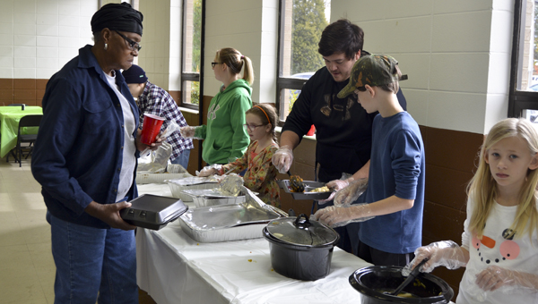 Skylar Lansdell, Dison Barbaree and Maci Barbaree help serve a Thanksgiving meal to members of the community. The fourth annual event is sponsored by Grace Fellowship Church and Through the Grace of God Ministries.