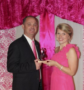 Chilton County Commissioner Joseph Parnell accepts a trophy for being named Chilton County's Man in Pink from Hannah Little, Chilton County Relay For Life Event Leadership Chair. (Contributed)