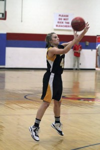 MacKenzie Glass aims the ball as she shoots a three-pointer.