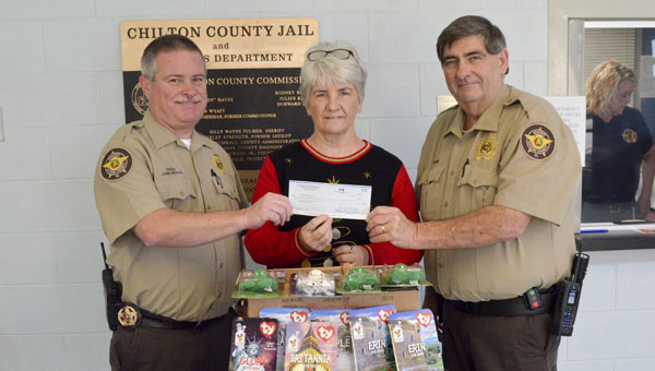 """United Way board chairman Yolanda Boggs (center) presents a $1,000 check to John Shearon and Warren Garris for the 13th annual """"Operation: Santa Claus."""" (Photo by Emily Reed)"""