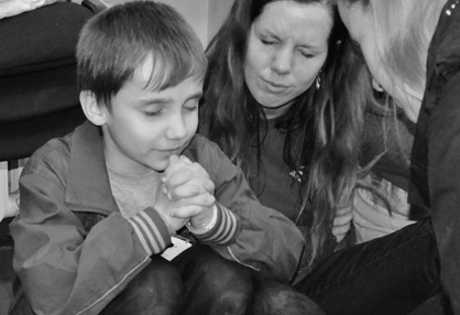 Moment of prayer: Bridges of Faith staff member Jennifer Taylor prays with an orphan during an outreach in Ukraine this past March.