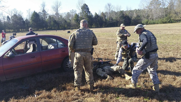 Keith Avery goes through the process of providing medical aid to Josh Hubbard (ground) as Todd Ingram and Kenneth Casey observe during a portion of a training exercise. (Photo by Anthony Richards / Advertiser)