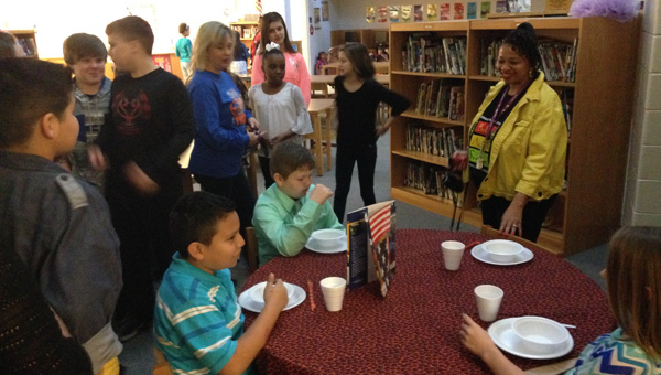 """All together: Teacher Pamela Smith (right) and Clanton Intermediate School students look on as Janie Downs, Ryan Gray and Jesus Roman portray a group of mixed ethnicity friends eating a meal together during a black history """"living museum"""" on Feb. 26. (Photos by Stephen Dawkins)"""