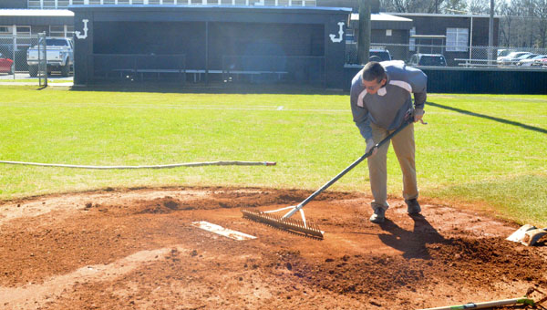 Jemison head coach Jason Easterling rakes the clay on the pitching mound in preparation for the Panthers' home opener against Shelby County on Feb. 19. (Photo by Anthony Richards / Advertiser)