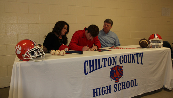 Corbin Bice signs Tuesday to play football and baseball at Huntingdon College with his parents Sonja Bice (left) and Jason Bice (right) by his side. (Contributed)