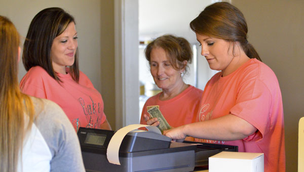 Cake Addiction owner Shelley Jones (center) helps customers on Friday with Candice Morrow (left) and Nicole Barrett (right). The store, located at the corner of Highway 145 and Ollie Avenue, opened two weeks ago. (Photo by Stephen Dawkins)