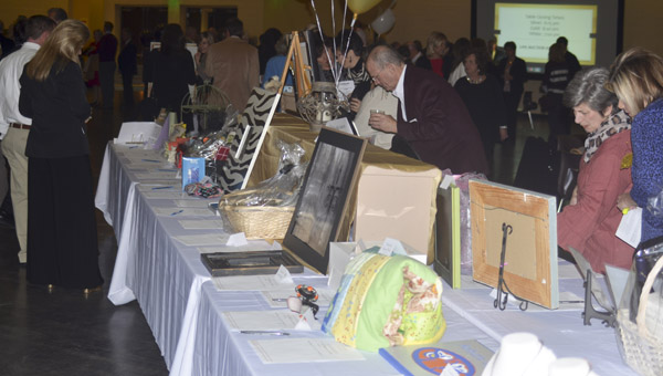 A table full of items gets looked over by event attendees during the silent auction portion of Flutter 2016 on Feb. 4. (Photo by Anthony Richards / Advertiser)
