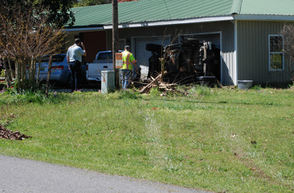 The vehicle veered between a power pole and its guy-wire before striking the house.