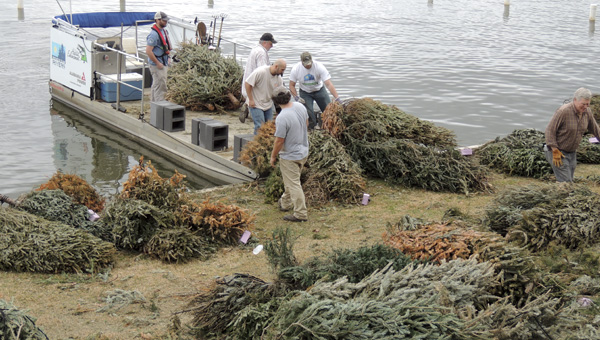 Alabama Power and volunteers from the Lake Mitchell Home Owners and Boat Owners Association, pictured in 2015, will drop Christmas trees into Lake Mitchell March 15 to form new habitats for fish.  (Contributed Photo)