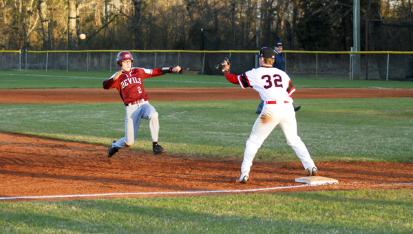 Maplesville's Aaron Dunkin begins to slide into third base in an attempt to beat the relay throw during a doubleheader against Holy Spirit on Friday.  (Photo by Anthony Richards / Advertiser)