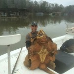 Wes Prewett poses with an alligator snapping turtle that he caught on March 4 in Blue Creek. (Photo Contributed)