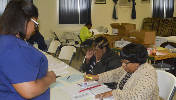 Poll workers Betty Reid (center) and Johnnie Bryant (right) check voter Destanie Karoma's name off the list at the American Legion Post 6 voting precinct in Clanton on Tuesday. (Photo by Stephen Dawkins)