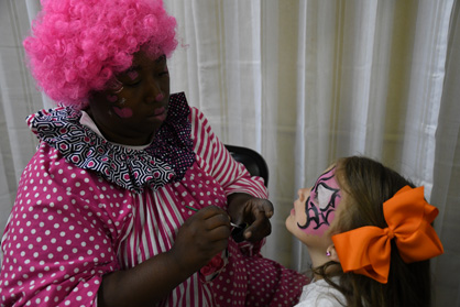Painted on: Elizabeth Eason (right) has her face painted by Pinky the Clown.