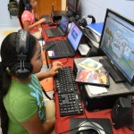 Digital lesson: Ashly Tello (front) and Simoney Morales use a computer program Wednesday as part of an English language camp hosted by the Chilton County School System.