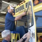 Mechanics Glen Johnson and Mike Thomas perform maintenance work on a Chilton County school bus. (Photo by Scott Mims)
