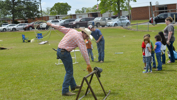 """Michael Patterson and Zane Smith teach proper roping technique to Thorsby students during """"Farm Day."""" (Photo by Anthony Richards)"""