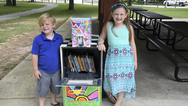 """Lincoln and Grace Bingham stand beside the """"Little Free Library,"""" which is now open for business under the pavilion at Richard Wood Park in Thorsby. (Photo by Anthony Richards)"""
